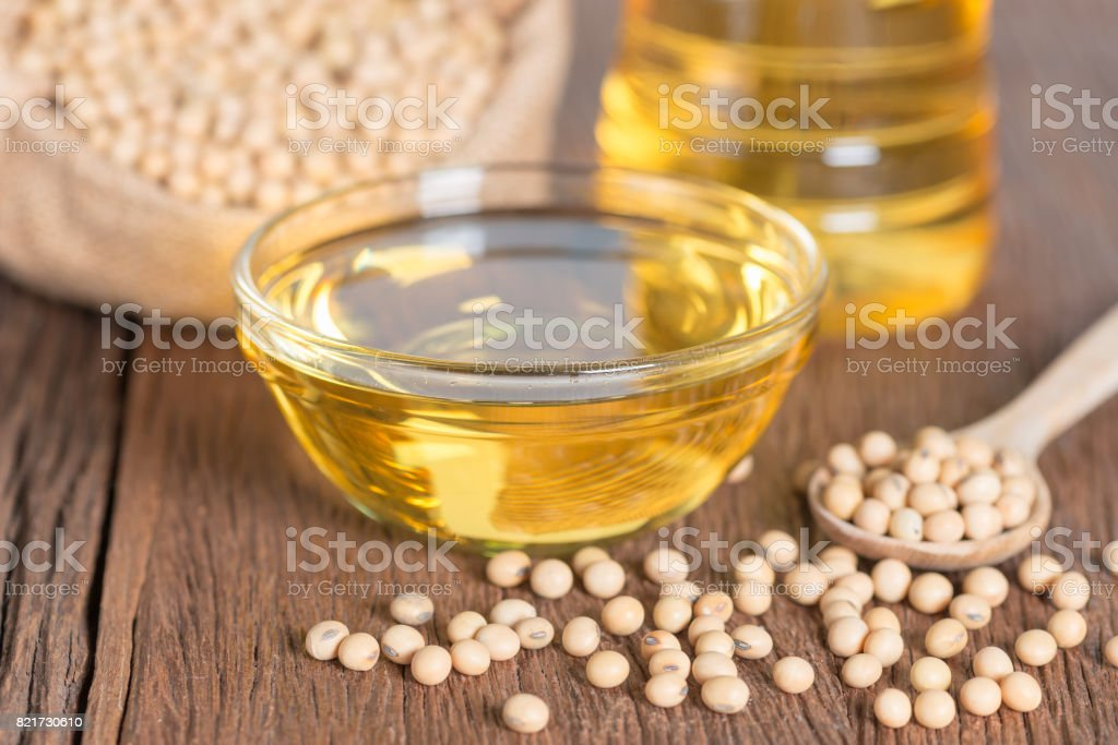 Soybean oil and Soybean on wooden table. stock photo