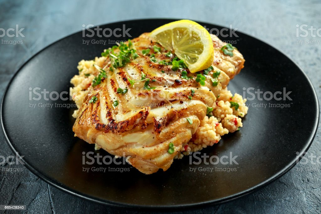 Soy-glazed cod loin fillet with cous-cous salad on black plate stock photo