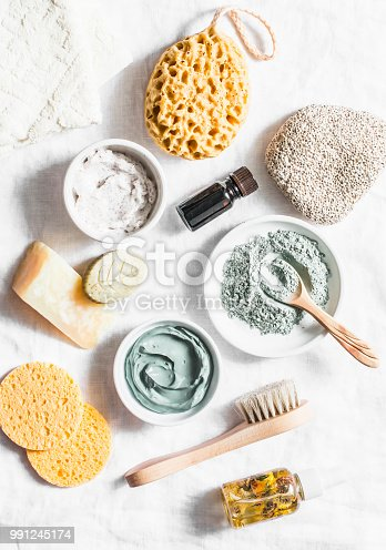 istock Spa accessories - nut scrub, sponge, facial brush, natural soap, clay face mask, pumice stone, essential oil on a light background, top view. Healthy lifestyle concept. Beauty, skin care. flat lay 991245174