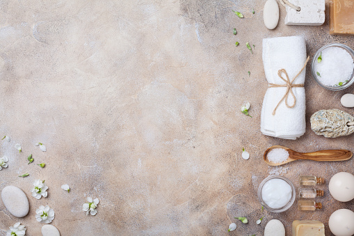 Spa and beauty conceptual stone background from handmade body care and aromatherapy supplies decorated flowers. Top view. Flat lay style.