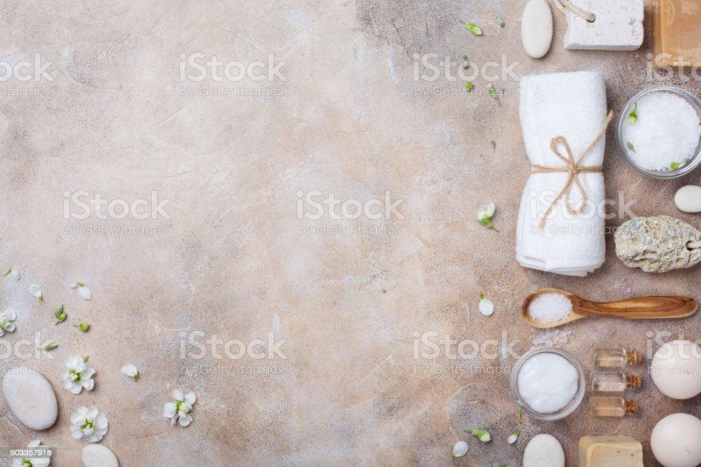 Spa and beauty conceptual stone background from handmade body care and aromatherapy supplies decorated flowers. Top view. stock photo