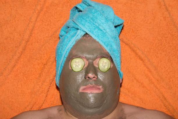 spa und gesichtsbehandlungen. lustige dicke mann und lehm maske. - gurkenmaske stock-fotos und bilder