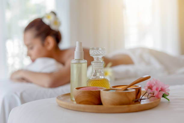 spa and massage elements, aroma salt, herbal oil, young woman relaxing in background, spa treatment and aromatherapy concept, selective focus - thai massage stock photos and pictures