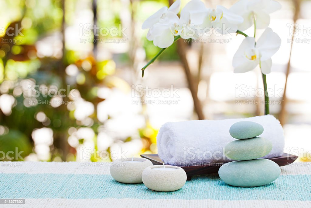 Spa and wellness massage setting with candle, towel and stones stock photo