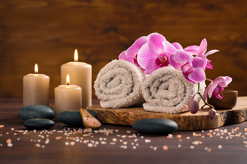 Spa setting with brown rolled towel, orchids and candles on wood. Relaxing spa concept with candles, towels and hot stones massage with himalayan pink salt. Beautiful composition for beauty treatment in a spa.