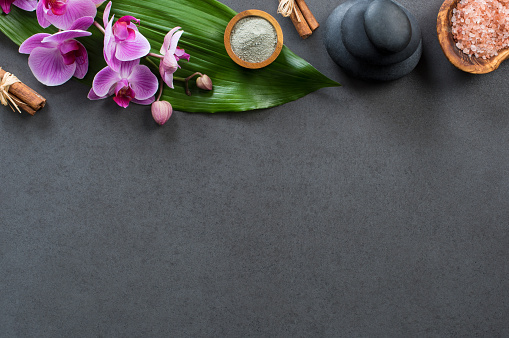 Top view of spa setting with hot stones, orchids and pink salt. High angle view of orchids with green leaf on blackboard with stacked hot stone for massage treatment. Luxury and elegant spa set with copy space.