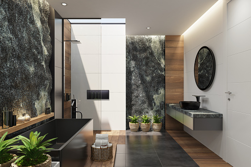 Trendy and modern home spa bathroom with matte black tiles, natural rock stone wall and roof natural light. Natural plants for cozy interior. Modern black bath tub. Wooden tiles on some walls. Candles light. Big roof window. Black matte stone floor. 3d rendering.