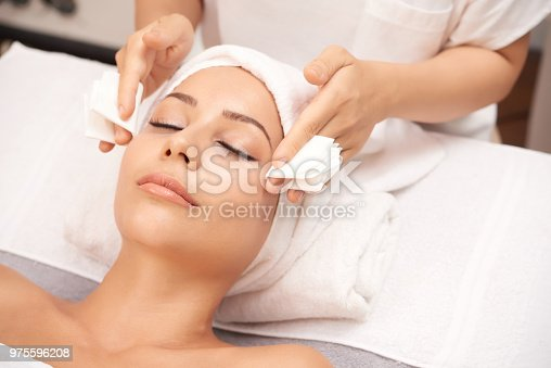 Beautician taking off excess of serum from face of client at the end of spa procedure