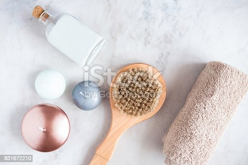 istock Spa beauty products on white marble table from above. Coconut oil, brush, candles, towel. Beauty blogger, massaging salon concept. 831672210