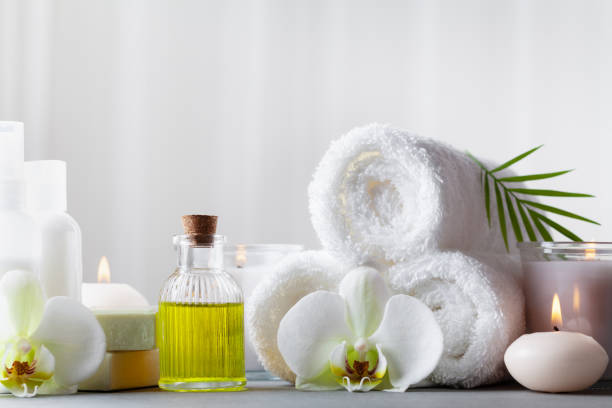 spa, beauty treatment and wellness background with massage oil, orchid flowers, towels, cosmetic products and burning candles. - massaggio foto e immagini stock