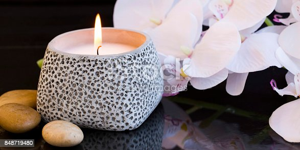Spa candle setting with orchid and massage stones