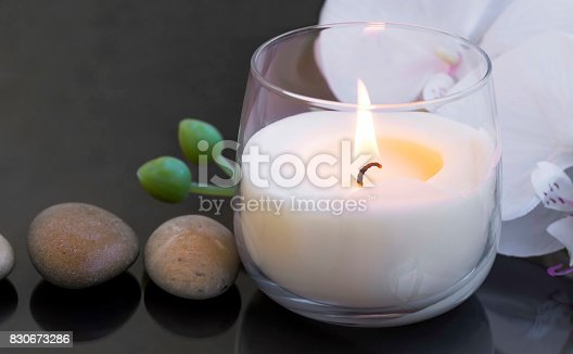 Spa candle , wellness and spa setting with massage stones and white orchid