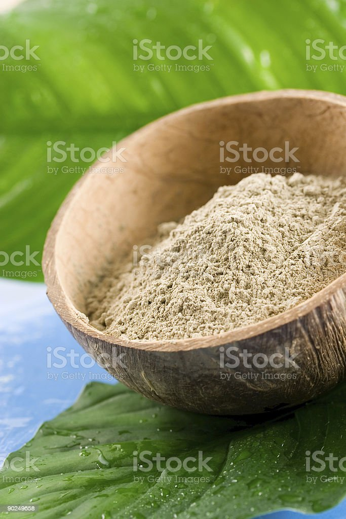 Spa clay on a coconut bowl on top of a banana leaf royalty-free stock photo