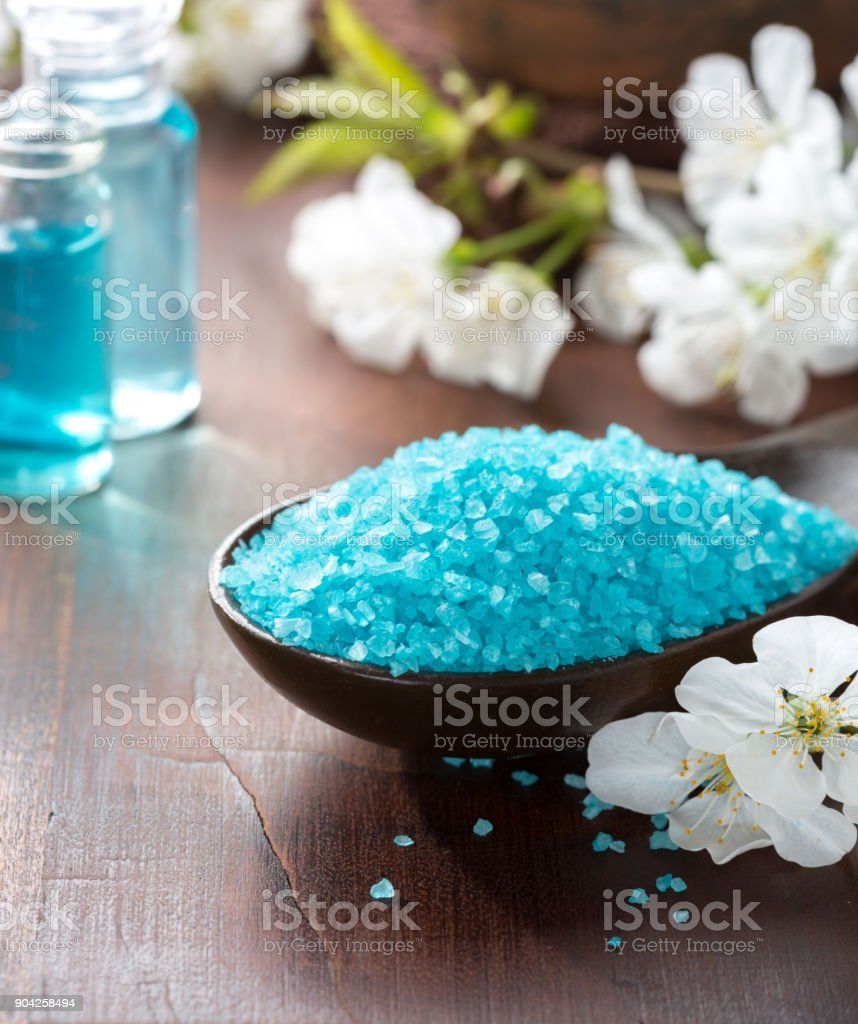 Spa concept. Mineral bath salts, shower gel, towels and spring flowers on the wooden table. stock photo