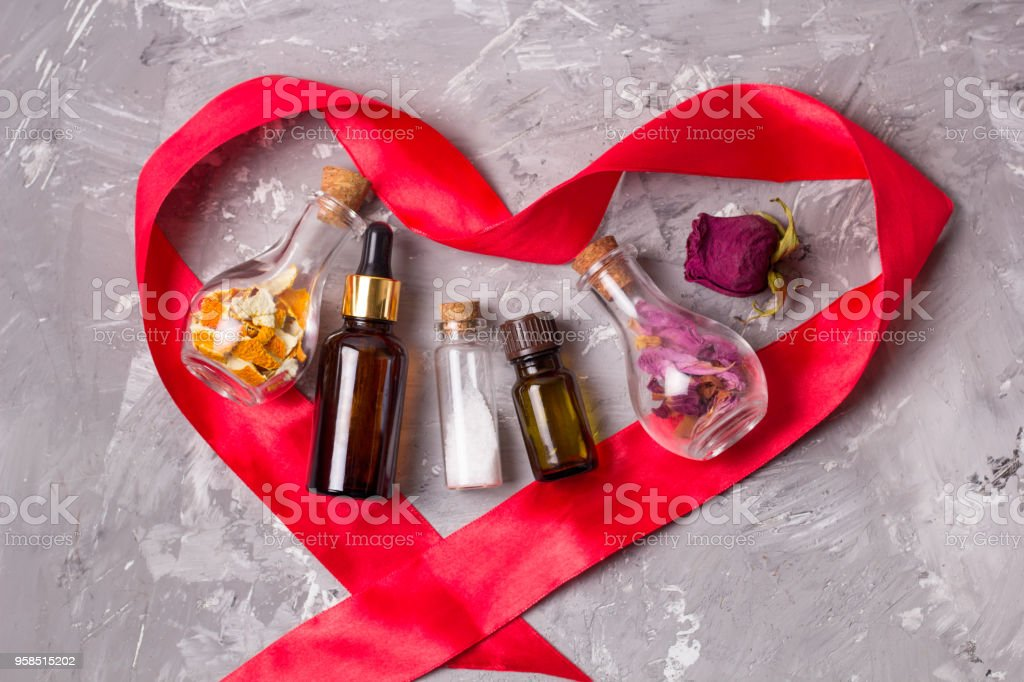 Spa concept of love for your body: heart shaped red satin ribbon aroma oils bottles,sea solt, dry rose petals and orange peel stock photo