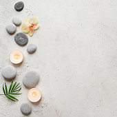 Spa concept on white stone background, palm leaves, flowers, candles and zen like grey stones, top view, copy space.