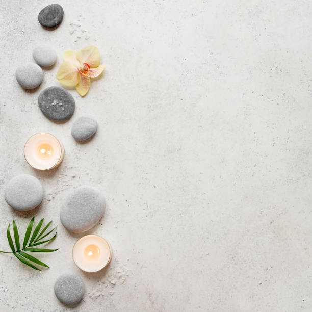 Spa concept Spa concept on white stone background, palm leaves, flowers, candles and zen like grey stones, top view, copy space. spa stock pictures, royalty-free photos & images
