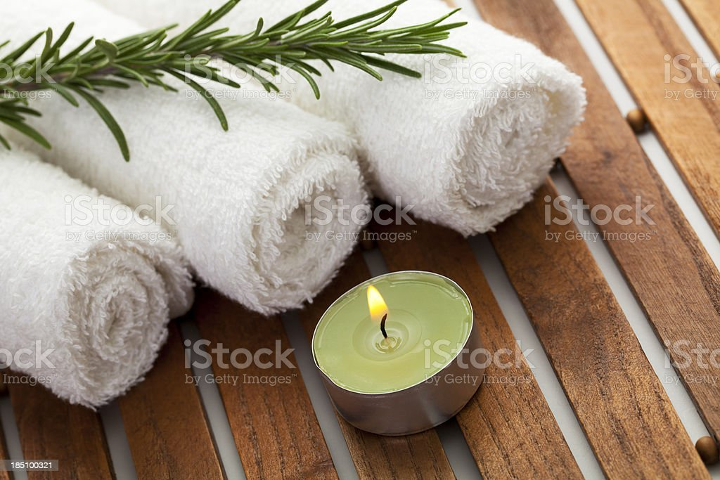 Spa concept with candle, towels, rosemary royalty-free stock photo