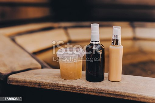 1042453716 istock photo Spa cosmetics in brown and yellow bottles on wooden background. 1173680312