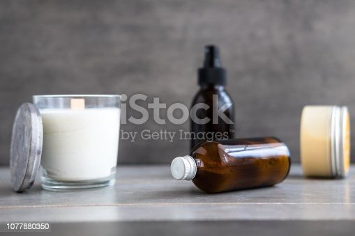1042453716 istock photo Spa cosmetics in brown bottles with candle 1077880350