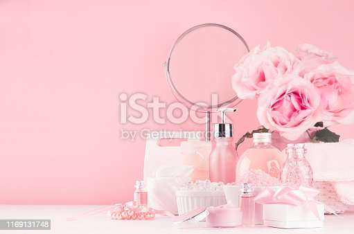 1056636898 istock photo Spa cosmetics products, round mirror, roses in pastel pink and silver color - cream, bath salt, essential oil, soap, bottle, bowl, towel on white wood shelf. 1169131748