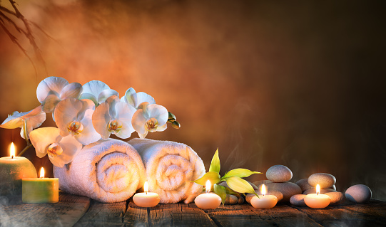 Two Towels, Bamboo, candles and pebble of Stones For Natural Massage