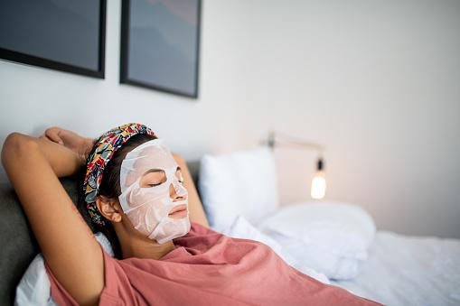 Young Latin woman applying face mask