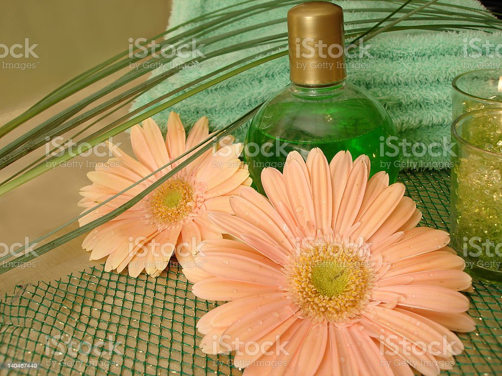 Spa essentials (bottle of shampoo and towel with flowers) royalty-free stock photo