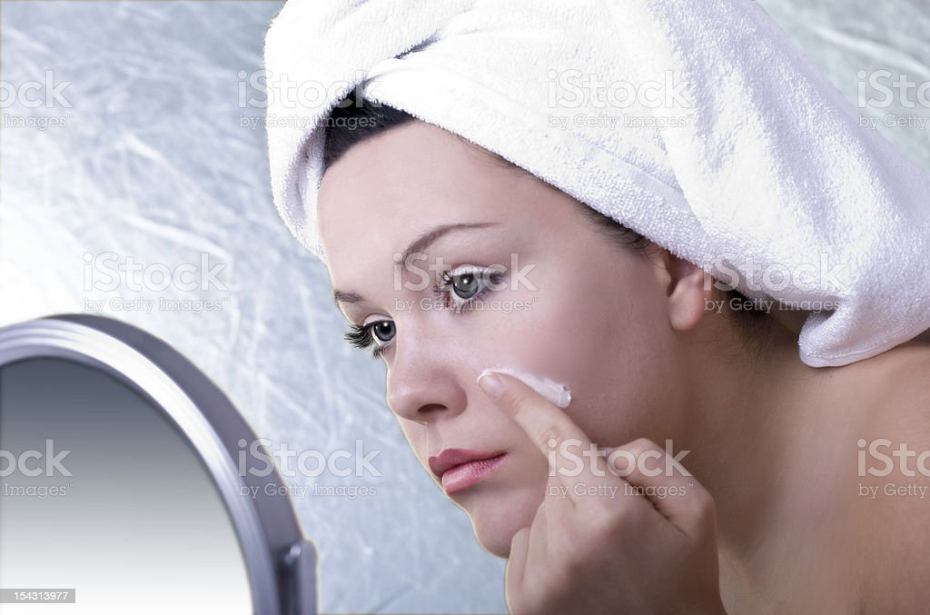 Spa girl putting cream on her face royalty-free stock photo