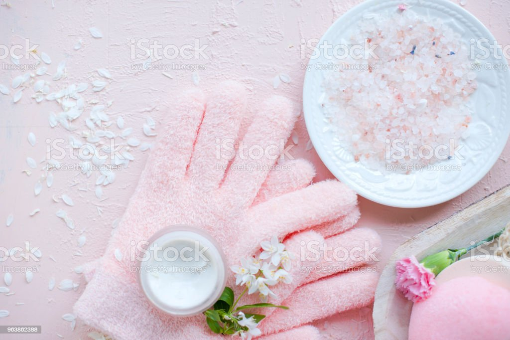 spa hand care, sea salt and gloves. The flowers are white. Pink background. - Royalty-free Archival Stock Photo