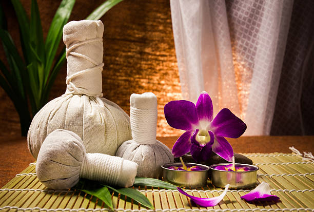 spa herbal compressing ball with candles and orchid - thai massage stock photos and pictures