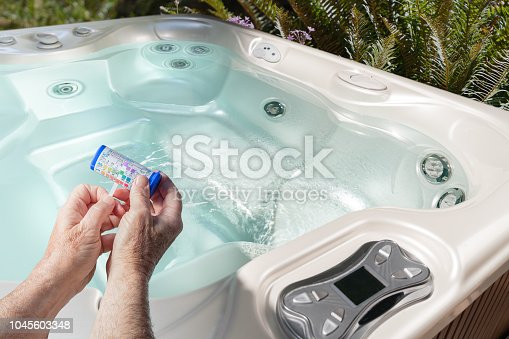 Test strips for spa pool testing pH, chlorine, bromine, alkalinity, color reading outdoors hot tub
