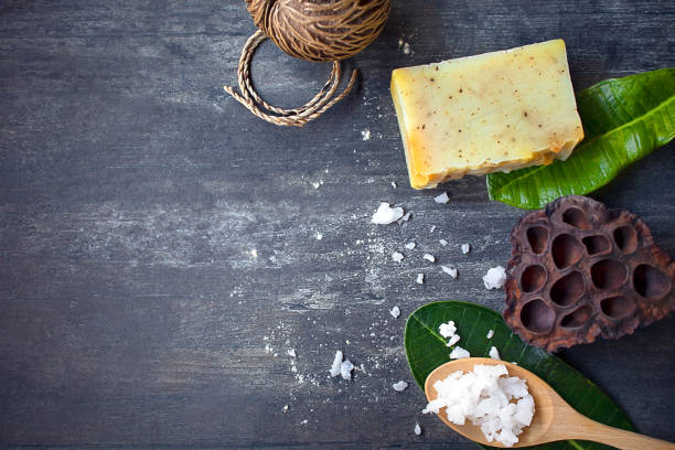 Spa ingredients, white salt, yellow homemade soap, tropical green leaves and little dry coconut on dark wooden board for copy space, spa, health and natural concept stock photo