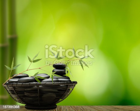 Massage Stones and Golden Bamboo against a Soft Green Background.