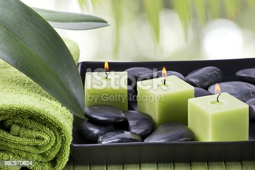 first floor with black stones for massage therapy, scented candles and towel in a spa environment