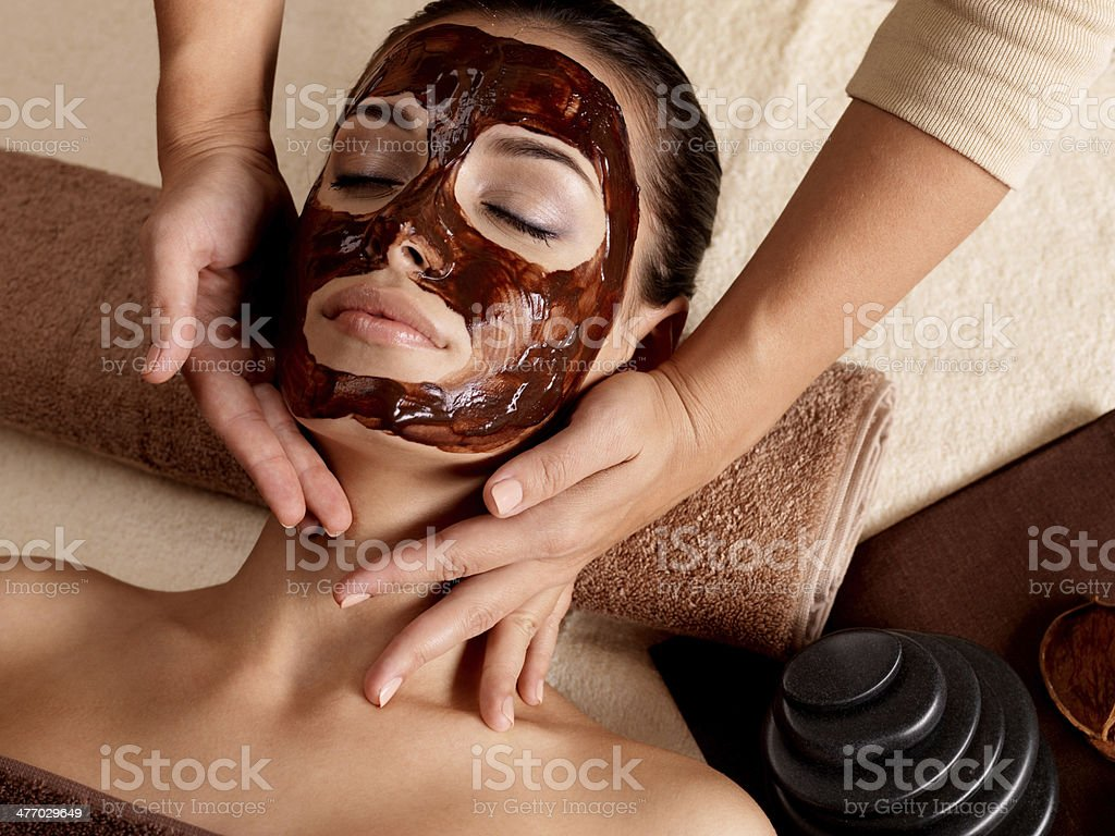 Spa massage for woman with facial mask on face royalty-free stock photo