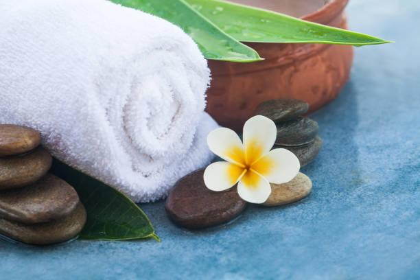spa-objekte und tropischen blumen für healhy massage auf tisch - steingut geschirr stock-fotos und bilder