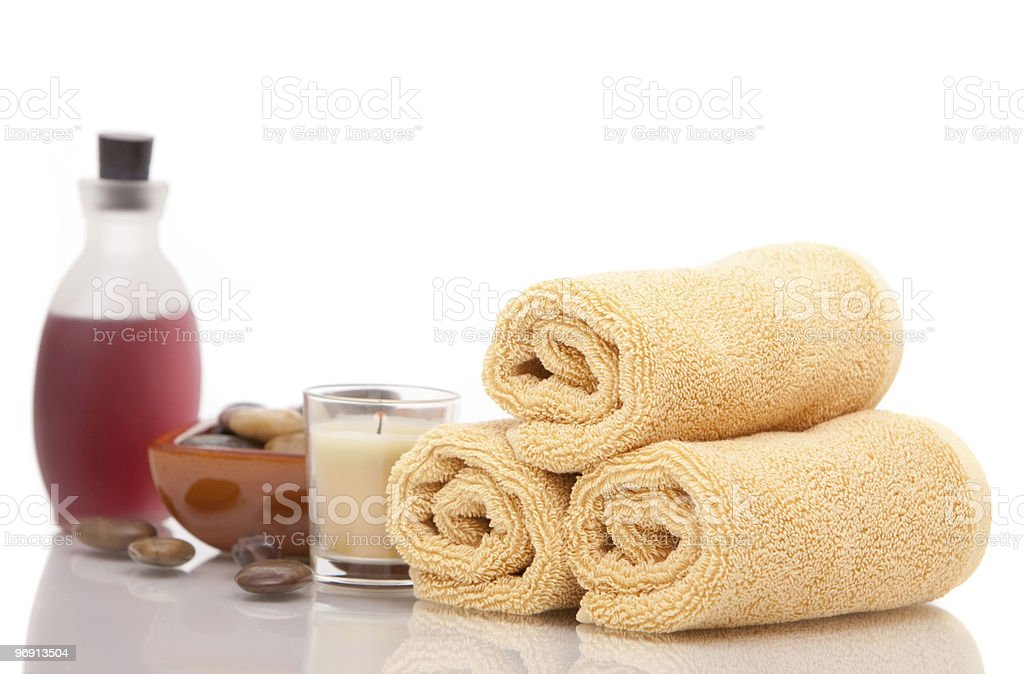 Spa oils, towels and candle on white background royalty-free stock photo