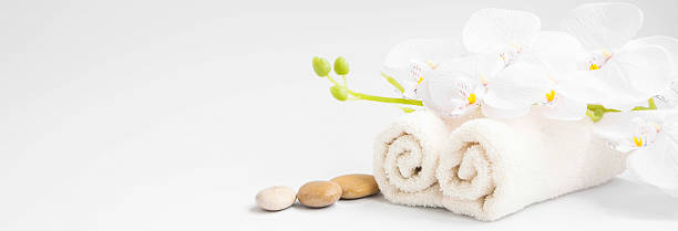 spa orchid with soft towels and massage stones setting - spa treatment stock photos and pictures