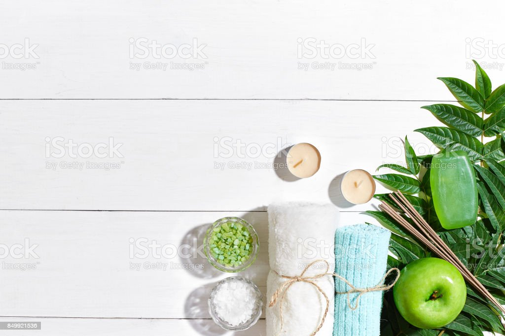 Spa products. Bath salts, soap, candles and towel. Flat lay on white wooden background, top view stock photo