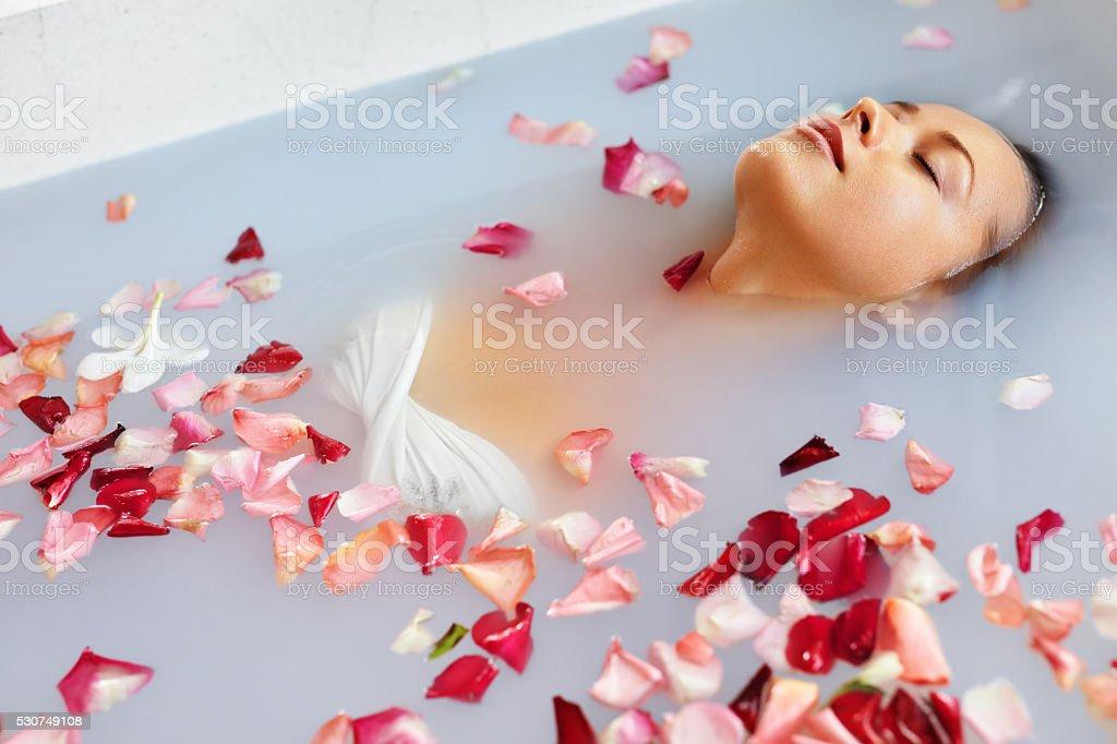 Entspannen Sie im Wellness Bad mit Blumenblüten. Frau Fitness, Beauty-Behandlungen und Körperbehandlungen – Foto