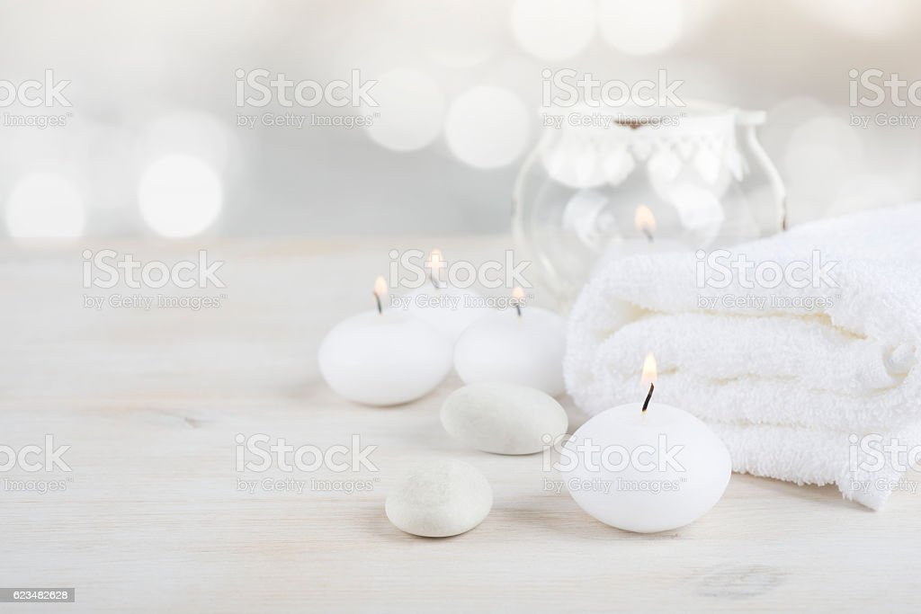 Spa resort therapy composition. Burning candles, stones, towel, abstract lights stock photo