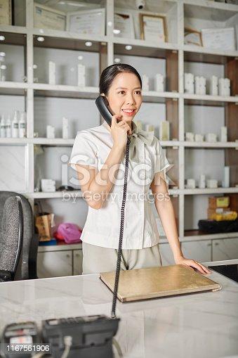1167562098 istock photo Spa salon worker calling on phone 1167561906