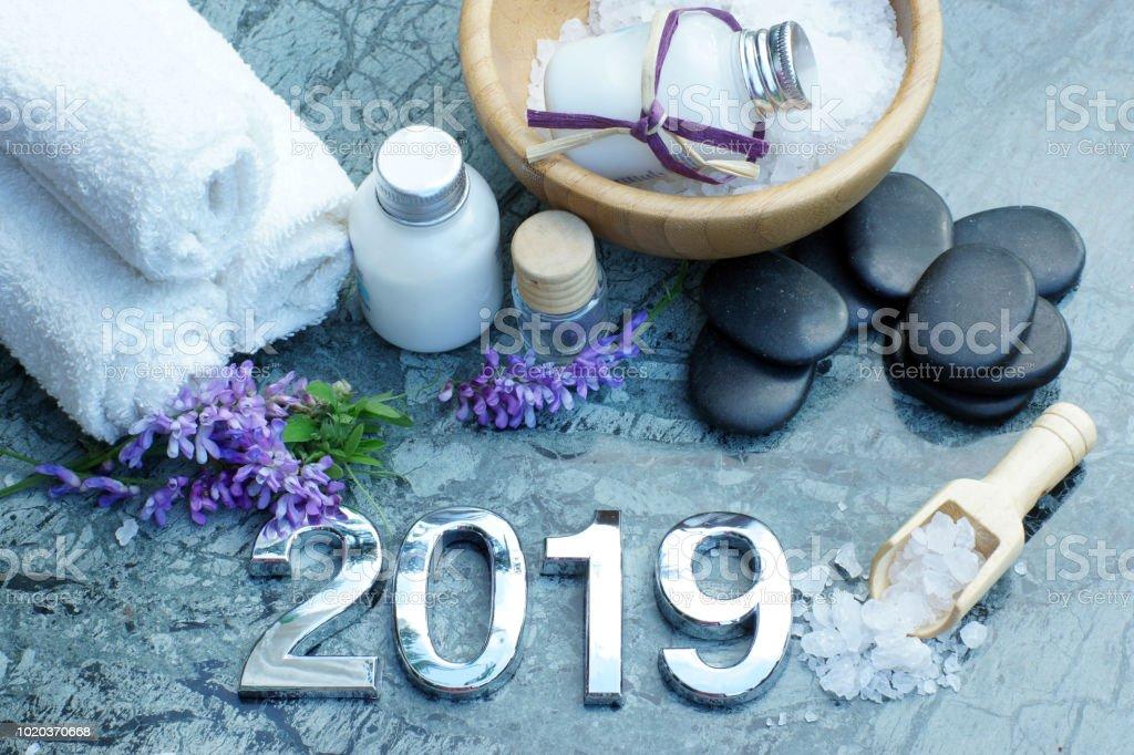 Spa pour 2019 avec lotion blanc et sel de bain, serviettes, préparés pour la procédure, des pierres noires pour un massage chaud se trouvent à proximité - Photo
