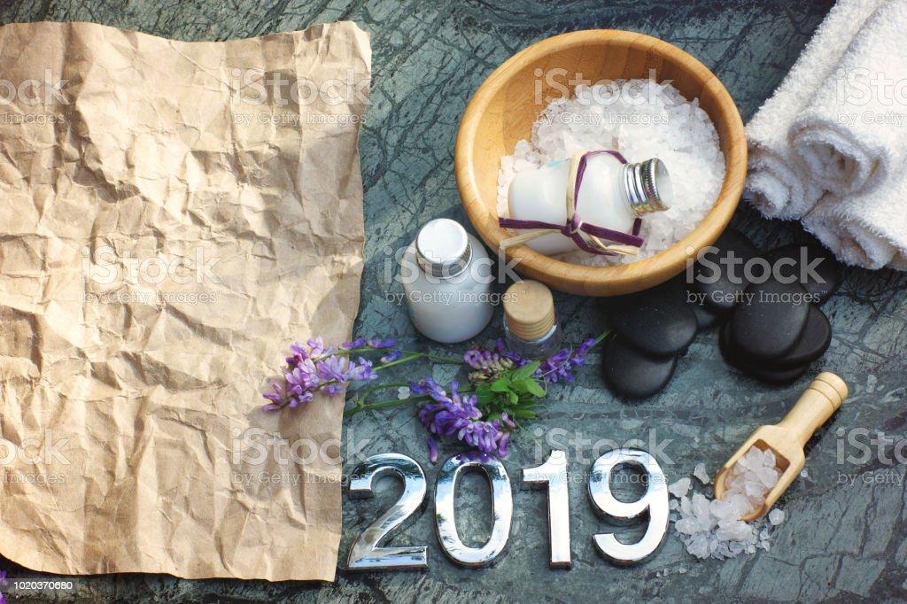 Jeu de Spa pour 2019 avec lotion blanc et sel de bain, serviettes, préparés pour la procédure, des pierres noires pour un massage chaud, sur la gauche il est un papier de métier pour votre texte - Photo