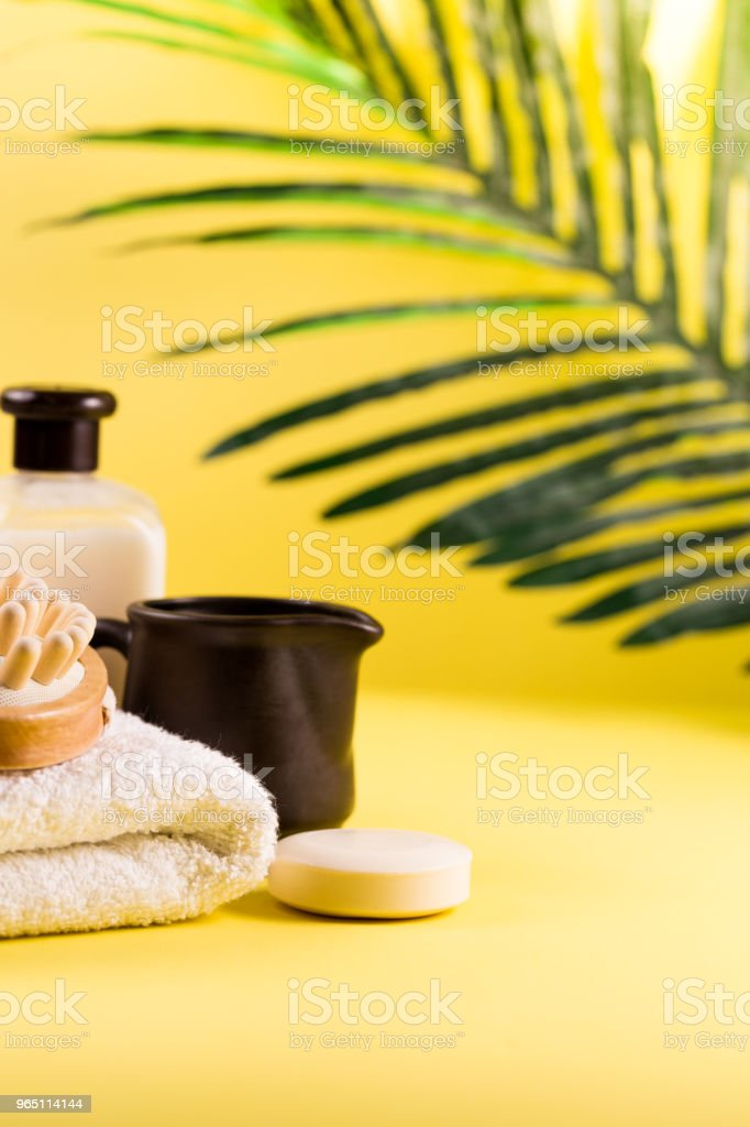 Spa setting concept, summer resort relaxation on yellow background, sea salt and oils with palm tree leaf zbiór zdjęć royalty-free