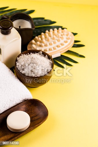 Spa Setting Concept Summer Resort Relaxation On Yellow Background Sea Salt And Oils With Palm Tree Leaf Stock Photo & More Pictures of Aromatherapy