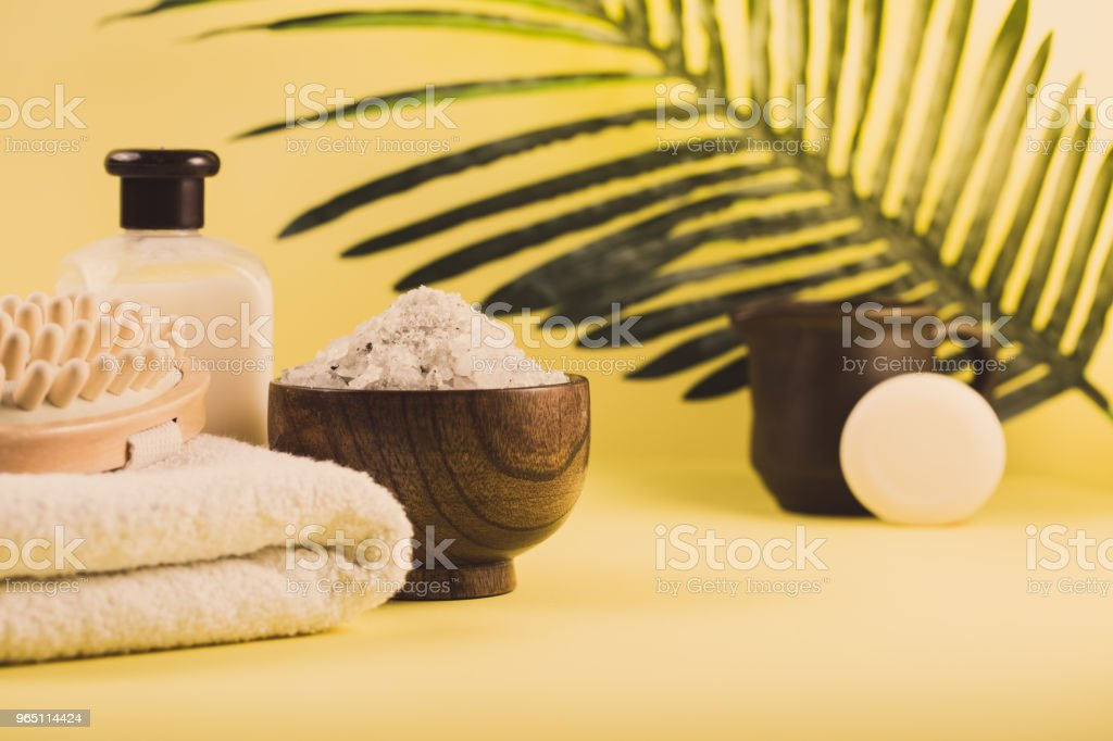 Spa setting concept, summer resort relaxation on yellow background, sea salt and oils with palm tree leaf royalty-free stock photo