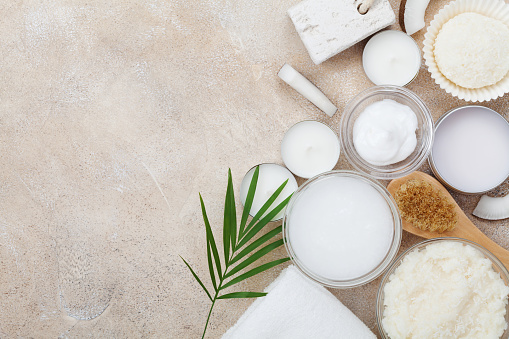 istock Spa setting from body care and beauty treatment. Organic coconut scrub, oil and cream on stone table top view. Flat lay. 1044097200