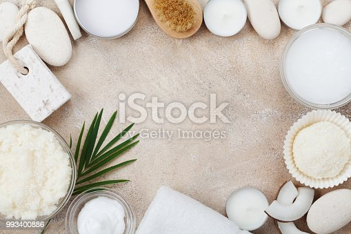 824824368 istock photo Spa setting from body care, wellness and beauty treatment. Coconut scrub, oil and cream on stone table top view. Flat lay. 993400886